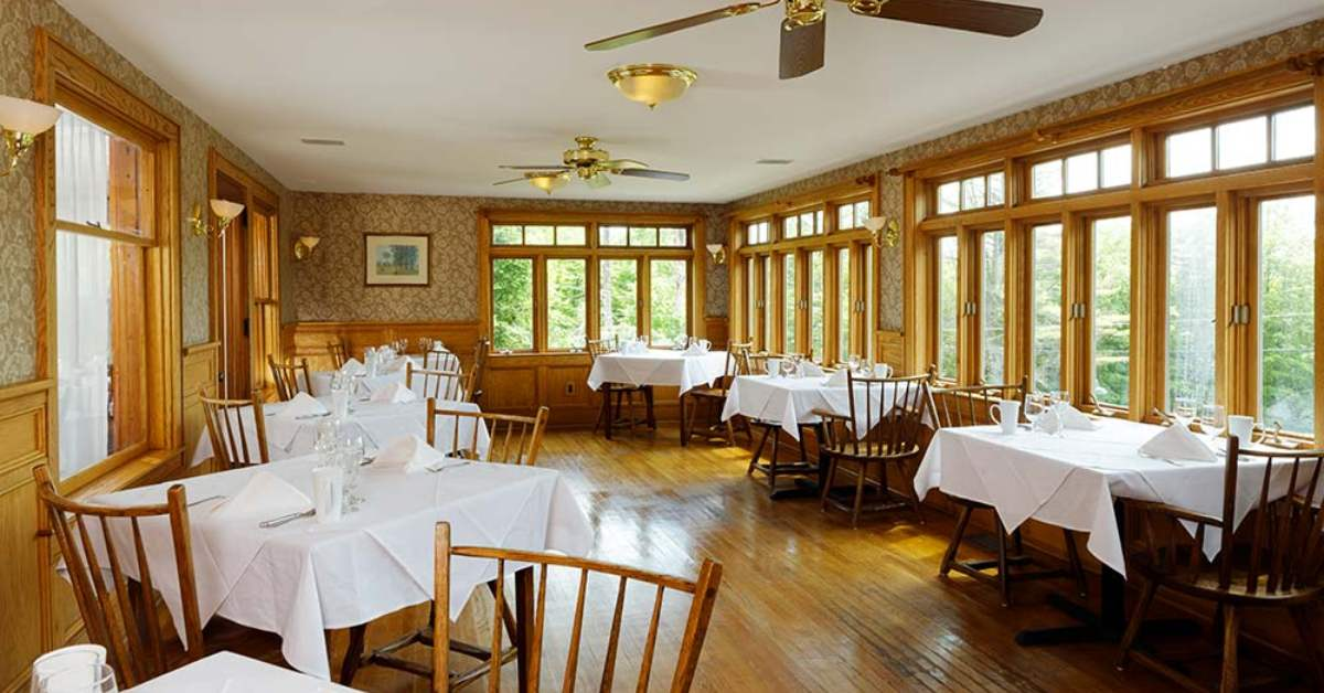 a dining room with lots of winds and tables with white tablecloths