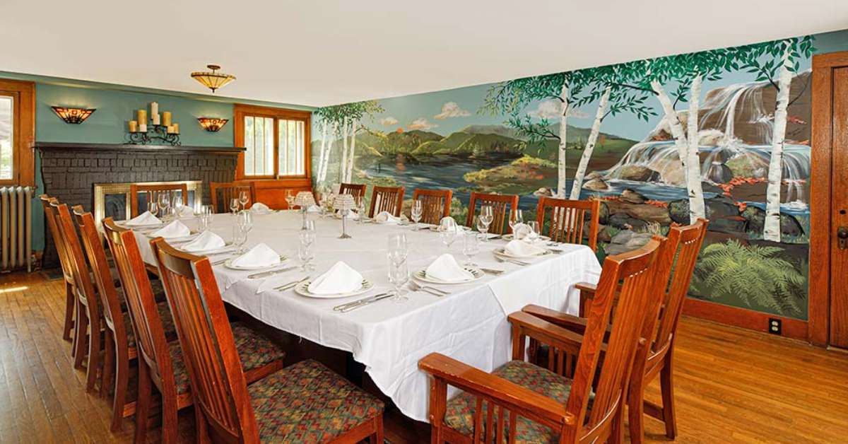 a room with a fireplace, a large table with dinnerware, and a wall sized mural of nature