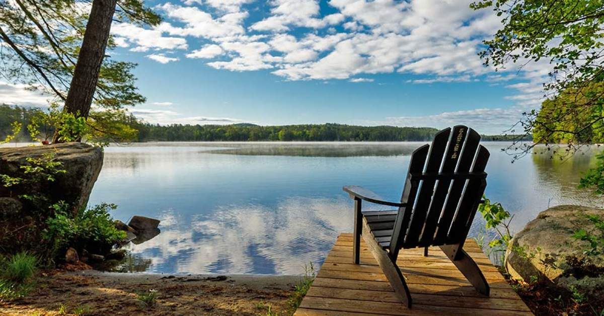 an adirondack chair on a boat dock by a lake