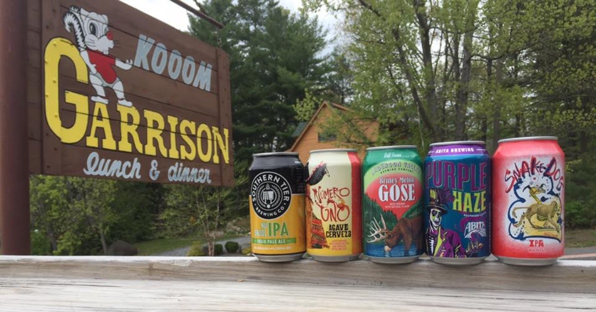 beer cans lined up by Garrison sign