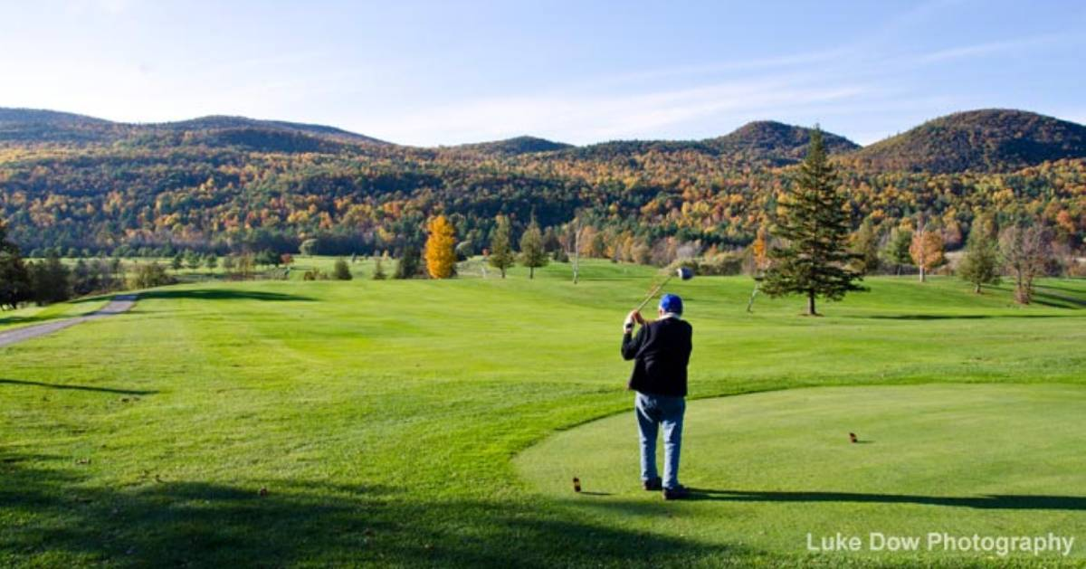 man on a golf course with fall foliage