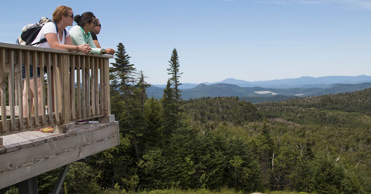 three hikers on a wooden overlook