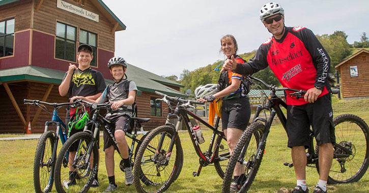 four mountain bikers near lodge