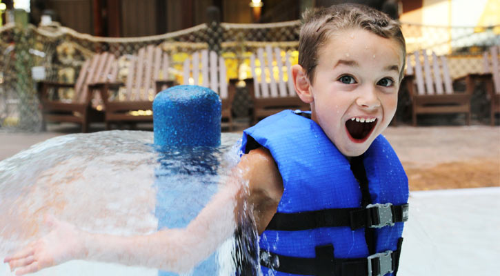 little boy with blue life jacket shows open-mouthed grin as he plays in the water park