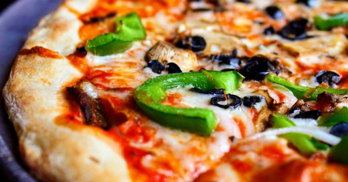 close up of pizza with green peppers, mushrooms, and black olives