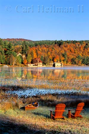 fall colors in the background with chairs and canoe near shoreline