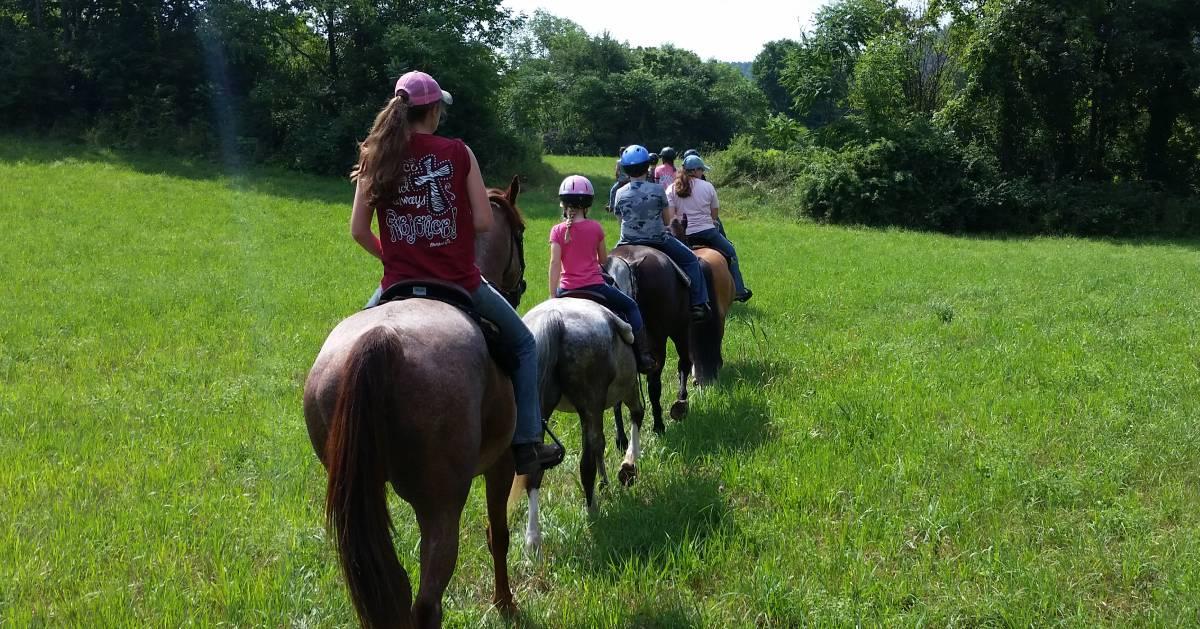 group, including kids, horseback riding