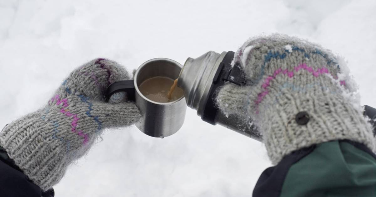 hands with gloves pouring hot chocolate