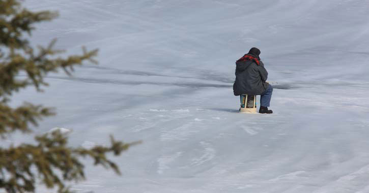 man sitting near ice fishing hole
