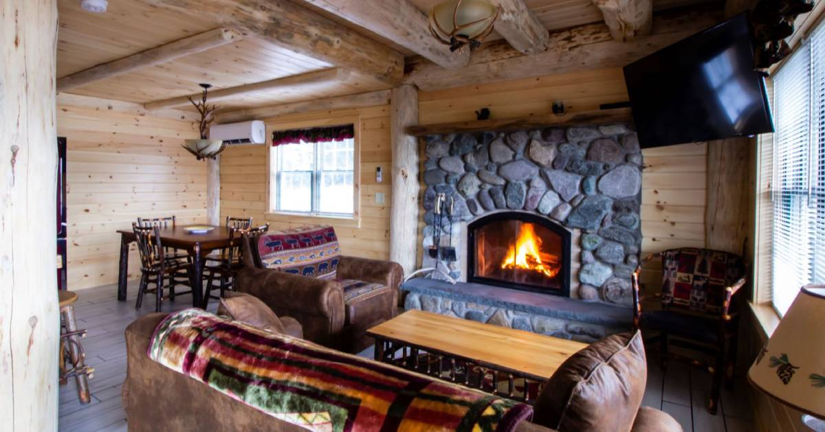 inside wooden cabin with a fire in the fireplace