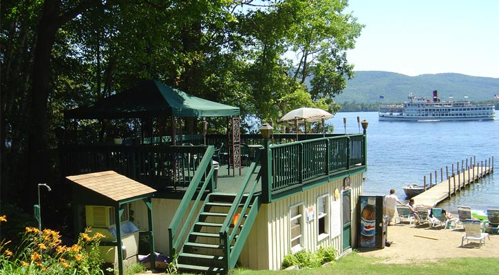 a back deck, private beach with a dock, and a steamboat cruise and mountain in the background