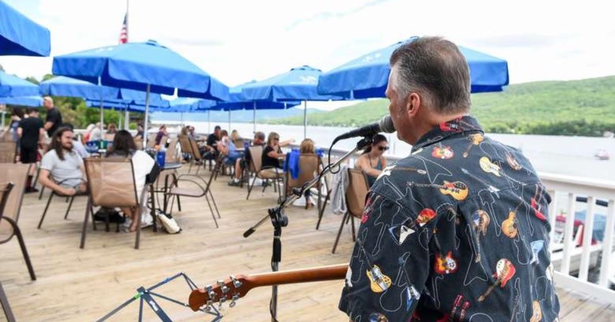 man playing guitar on restaurant deck
