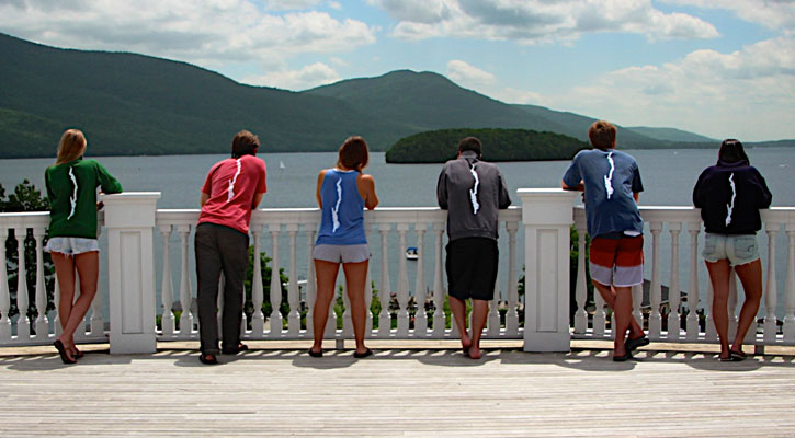 five people standing on a deck looking out at the water and they all have shirts with the shape of Lake George on