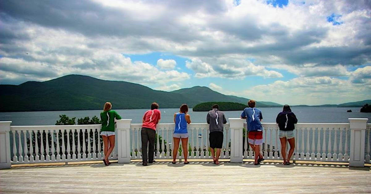 people looking out over lake, they're all wearing shirts with shape of Lake George on them