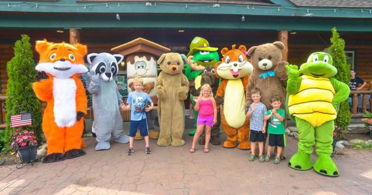 kids standing near costumed characters