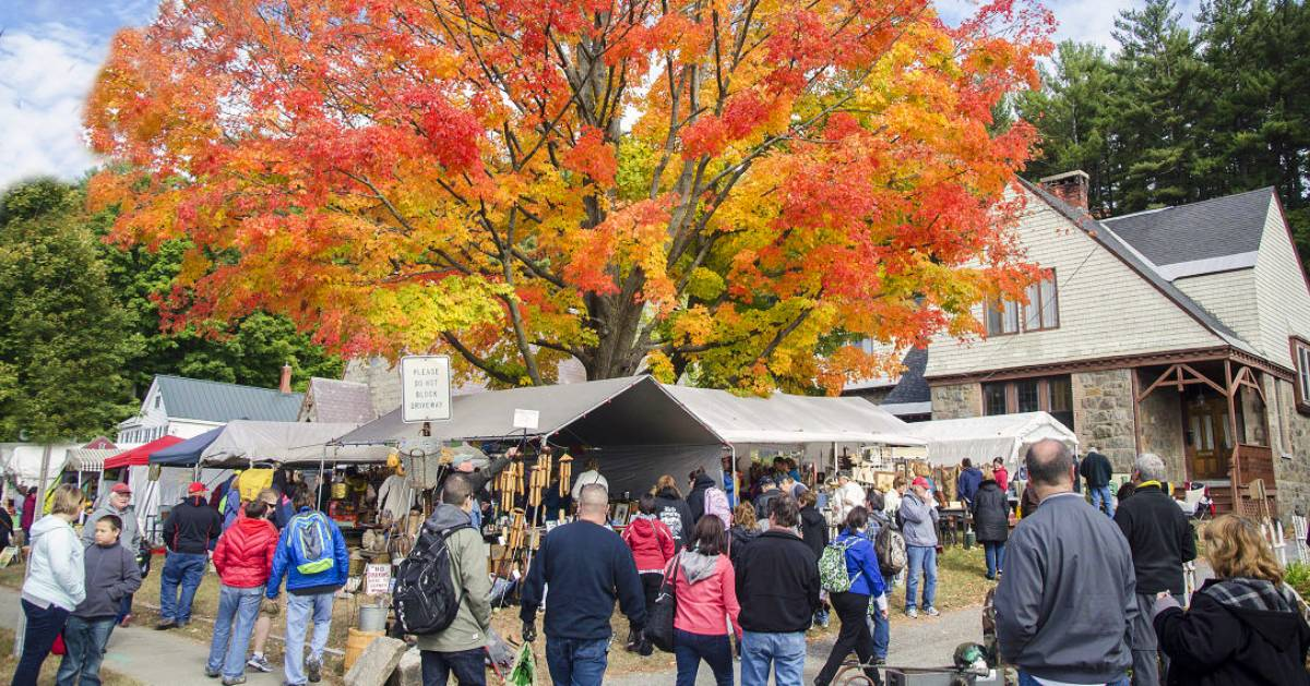 fall foliage on a tree and a garage sale happening nearby with a crowd of people