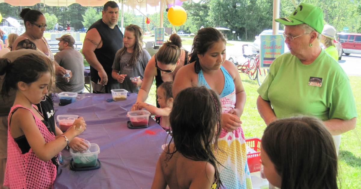 kids working on crafts at a birthday tent