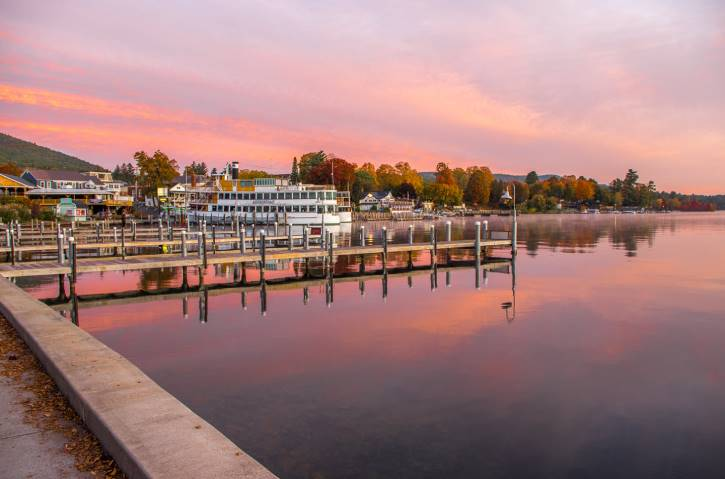 Pink sunrise over lake with fall foliage