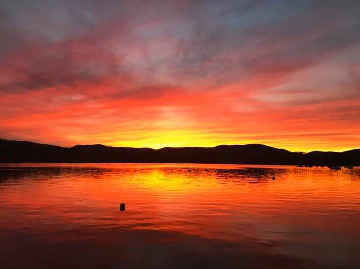 Yellow and orange sunset over lake with mountains