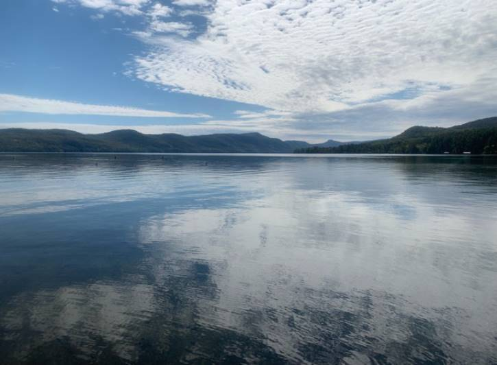 Blue sky with clouds reflecting on a lake