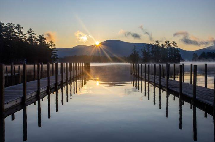 Sun rising behind mountains over lake with 2 docks