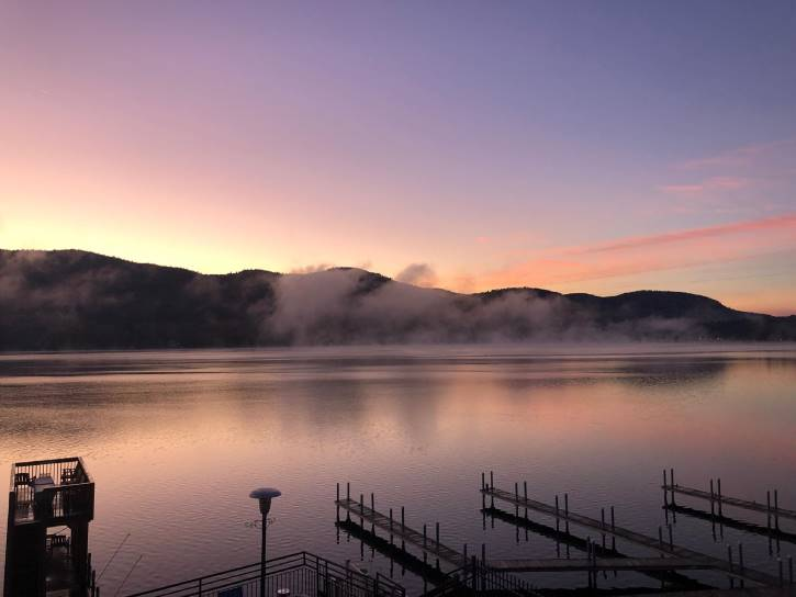 Pastel pink and blue sunrise over misty lake