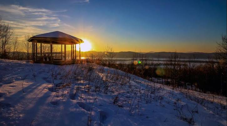 Gazebo pictured at sunset with snow and mountains in the background