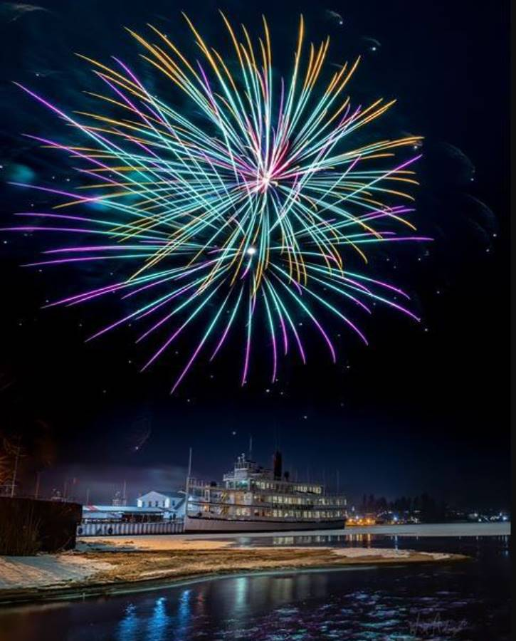 Colorful fireworks over steamboat on icy lake