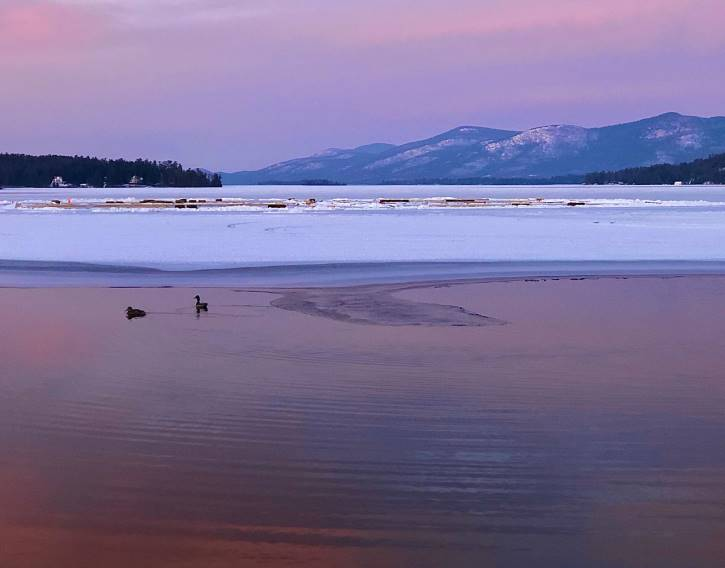 Purple sky reflecting off partially frozen lake