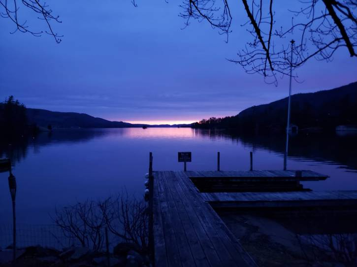 Dock on a lake with a blue and pink sunrise