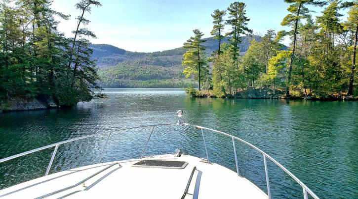 View from a boat on water with mountains and trees