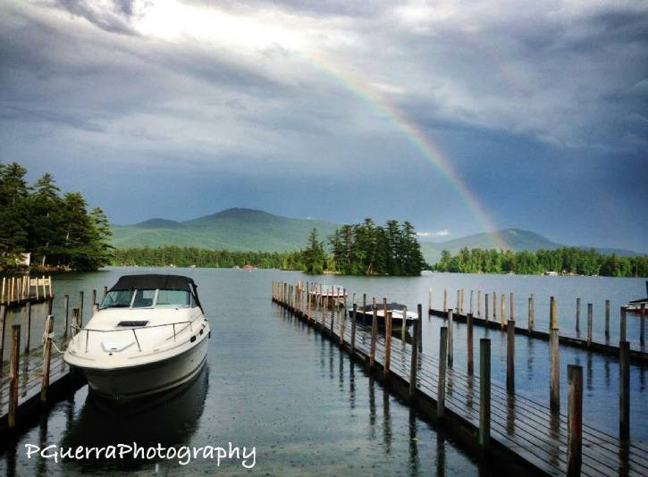 Rainbow over lake on a cloudy day with a boat and dock