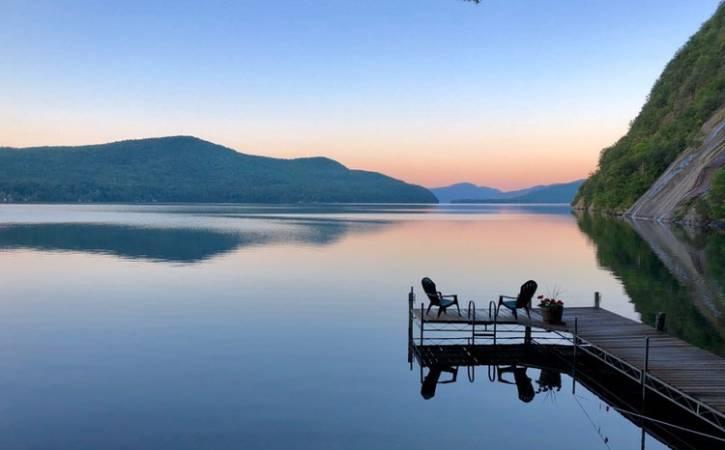 Sunrise over lake with dock & 2 Adirondack chairs