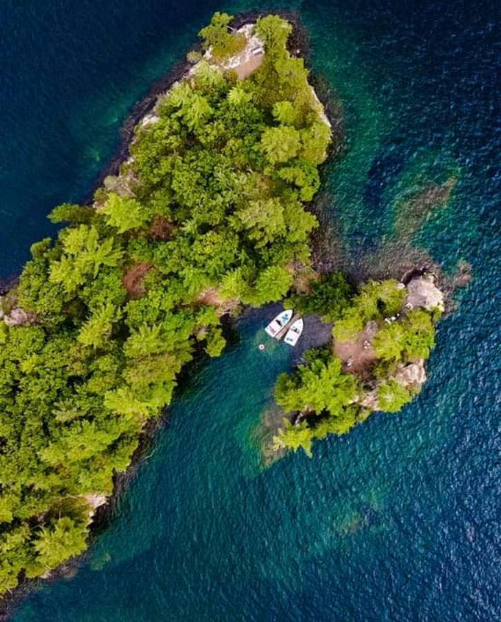 Aerial shot of a small island with two boats