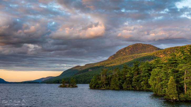 sun shining on mountain through clouds near lake