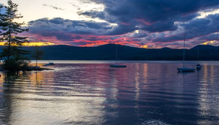 Colorful cloudy sky over lake with four sailboats