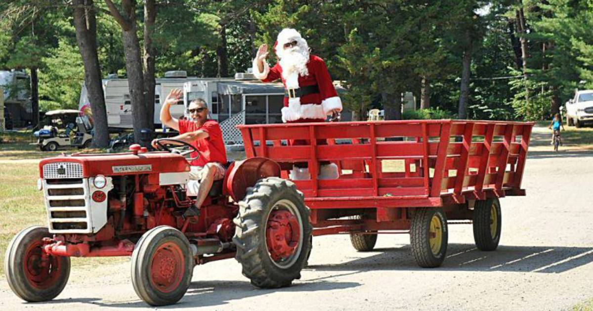 driving driving a tractor with santa in the back wagon