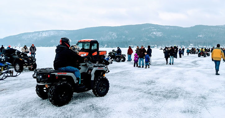 vehicles and people on frozen lake