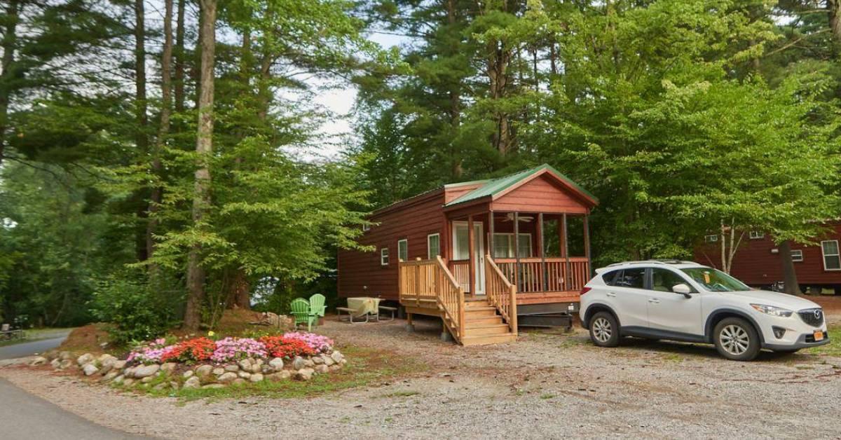 a car near a wooden cottage