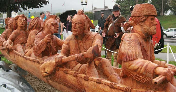 a large sculpture of Indians and trappers in a canoe with people standing around admiring it