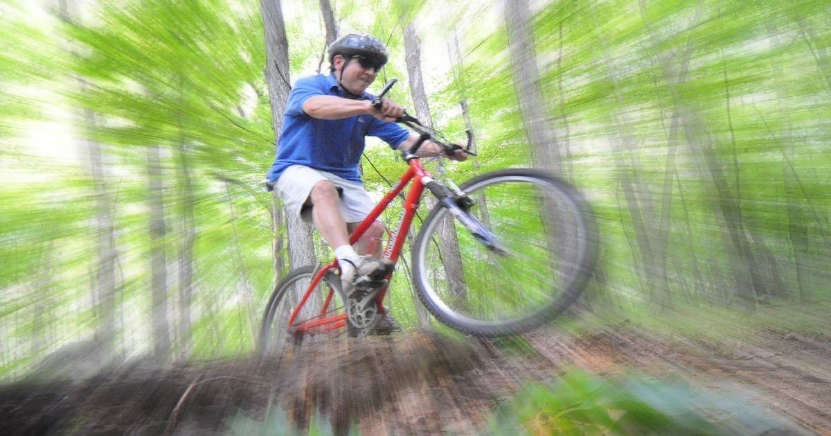 man bikes in the woods
