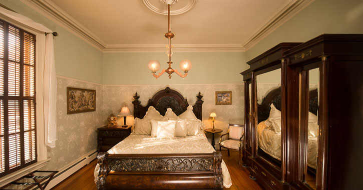 an elegant looking bedroom with a high ceiling, chandelier, etc