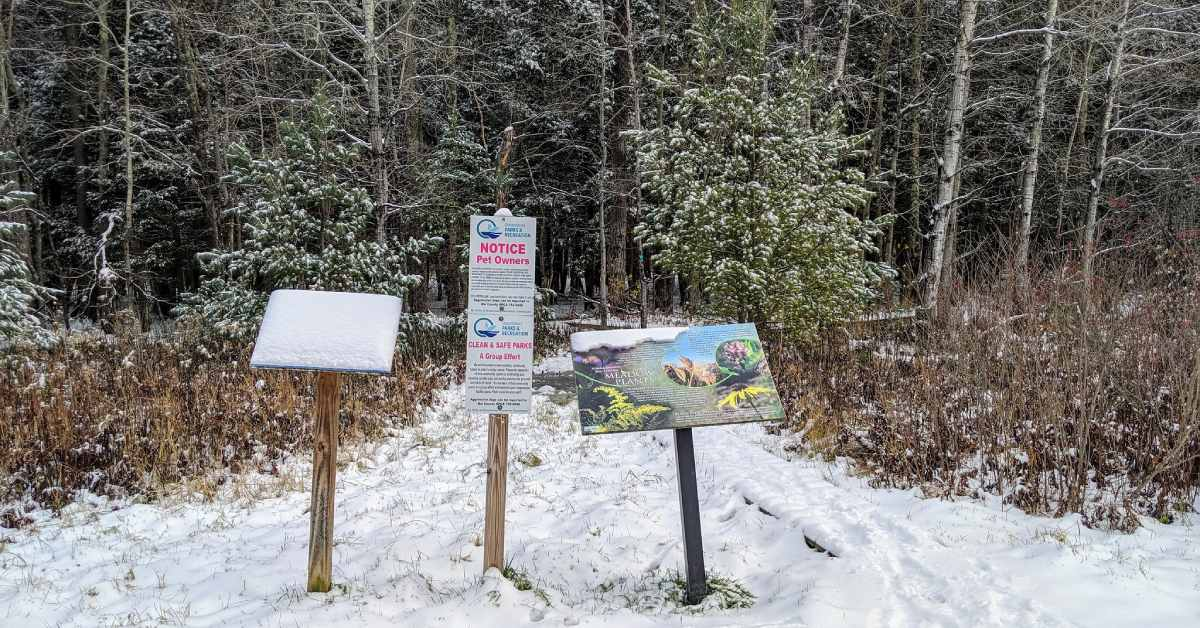 signs along a trail in winter with snow on the ground