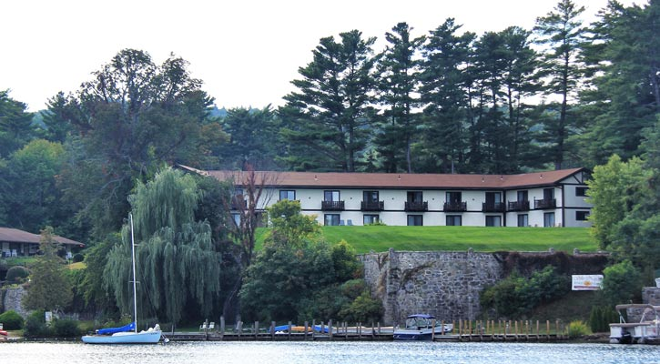 view of Melody Manor from the water with boats at the dock and a lot of trees on the property