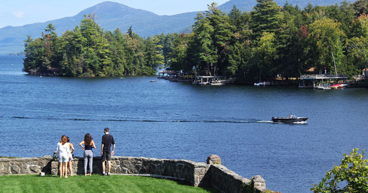 people standing by a stone wall looking out at the lake on a beautiful day