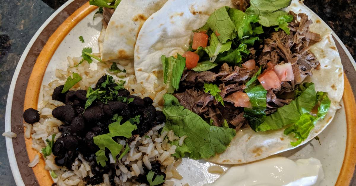 plate with beef taco and rice and beans