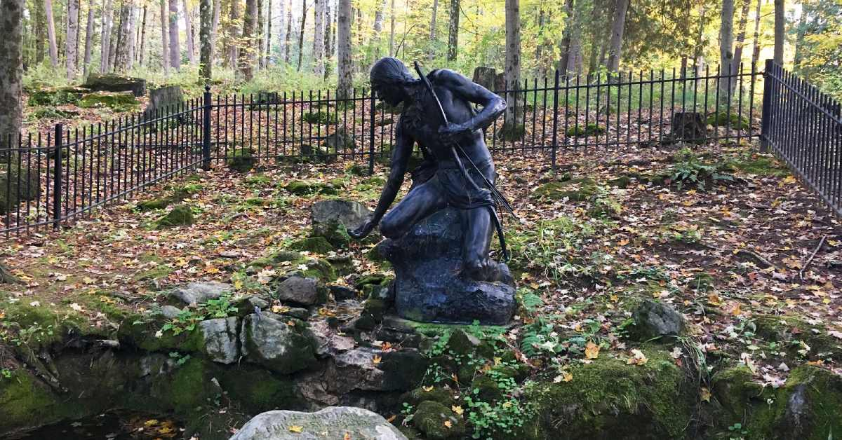 statue of mohawk warrior dipping his palm in the stream