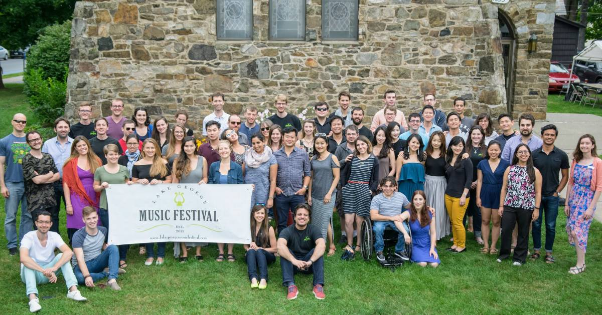 music festival group posing together with sign