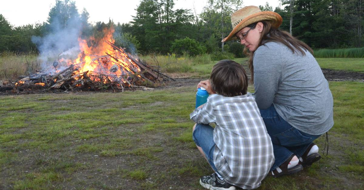 a woman and boy crouching near a bonfire