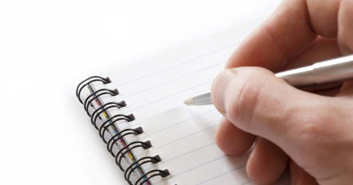 person writing on a notepad